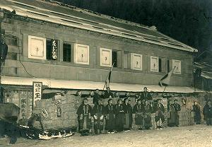 大正初期 明治40年に建設した石造りの店舗の前で。創業者藤井専蔵を従業員が囲む。